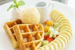 Belgian waffles with chocolate, bananas and strawberries. Stock Photo