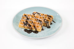 Belgian waffles with chocolate and powdered sugar on a blueish p Stock Image