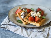 Belgian waffles with cream, chocolate and strawberries on a gray plate on a gray rustic background royalty free stock images