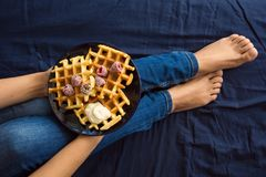 Belgian waffles with cream and frozen raspberries on blue ceramic plate in woman` s hands Royalty Free Stock Photography