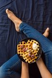 Belgian waffles with cream and frozen raspberries on blue ceramic plate in woman` s hands Royalty Free Stock Images