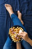 Belgian waffles with cream and frozen raspberries on blue ceramic plate in woman` s hands Royalty Free Stock Photo