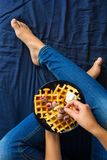 Belgian waffles with cream and frozen raspberries on blue ceramic plate in woman` s hands. Top view Stock Images