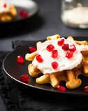 Belgian waffles with cream and pomegranate seeds on black background stock photo