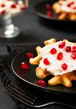 Belgian waffles with cream and pomegranate seeds on black background - close up vertical photography stock photos