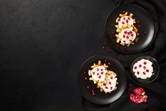 Belgian waffles with cream and pomegranate seeds on black background with copy space royalty free stock photos