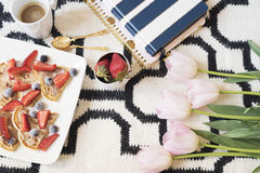 Belgian waffles on the floor. Coffee, berries, notebooks on Scandinavian rug. Pink Tulips and Gold Spoons. White black pattern and Stock Photography