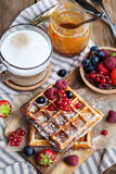 Belgian waffles with fresh berries and cappuccino Stock Photos