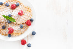 Belgian waffles with fresh berries on white wooden table Royalty Free Stock Images