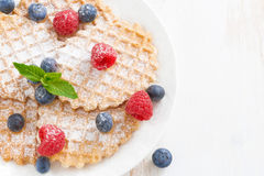 Belgian waffles with fresh berries on wooden table Stock Photography