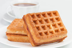 Belgian waffles. Fresh belgian waffles served on tabledesk with cup of tea Royalty Free Stock Photography