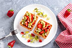 Belgian waffles with fruits strawberries and kiwi on white plate closeup. Tasty healthy breakfast stock photography