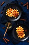 Belgian waffles with honey and cinnamon on dark blue textured background - fresh baked pastry with spices royalty free stock images