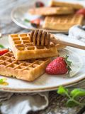 Belgian waffles with honey and strawberries on a white plate stock photos
