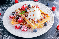 Belgian waffles with ice cream, chocolate sauce and fresh berries. Stock Images