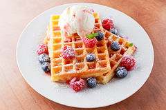 Belgian waffles with ice cream and fresh berries. Royalty Free Stock Photo