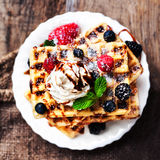 Belgian waffles with ice cream, fruits, syrup and icing. Homemad Stock Images