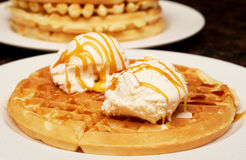 Belgian waffles with ice-cream and syrup. On white plate Royalty Free Stock Images