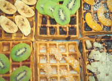 Belgian waffles with kiwi, bananas, oranges. coconut flakes and chocolate, homemade healthy breakfast, selective focus Stock Photo