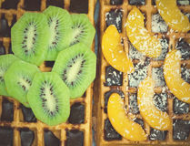 Belgian waffles with kiwi, oranges. coconut flakes and chocolate, homemade healthy breakfast, selective focus Stock Image