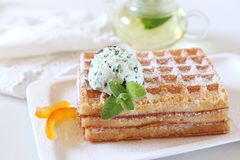 Belgian waffles with Mint Chocolate Chip Ice Cream and mint tea. Focus selective Royalty Free Stock Photo