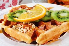 Belgian waffles with orange, kiwi, nuts on a plate close-up Stock Photos