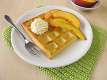 Belgian waffles with peaches and whipped cream Royalty Free Stock Photo