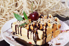 Belgian waffles with peanut chocolate sauce and cherries on a plate. In still life straw Stock Photo