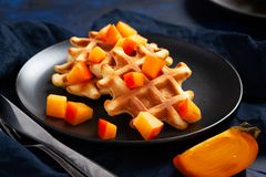 Belgian waffles with persimmon on black plate in dark mood style stock photos