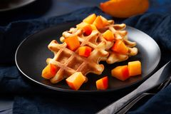 Belgian waffles with persimmon on black plate in dark mood style - close up horizontal photography stock image