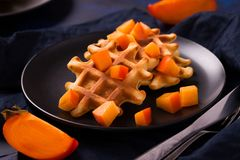 Belgian waffles with persimmon pieces on black plate in dark mood style stock photos