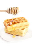Belgian waffles on a plate, stick for honey and honey Stock Image