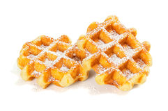 Belgian Waffles with Powdered Sugar. Two Liege style Belgian waffles on a white background with powdered sugar on top. Liege waffles are dense and chewy and made Royalty Free Stock Photo