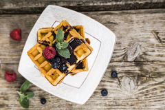 Belgian waffles with raspberries, blueberries and mint, covered Royalty Free Stock Photo