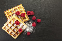 Belgian waffles with raspberries and icing sugar on slate backgr Royalty Free Stock Image