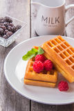 Belgian waffles with raspberries and mint for breakfast. Belgian waffles with raspberries and mint Stock Photo