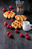 Belgian waffles with raspberries. Served with coffee pot and jug of milk over old wooden table Stock Images