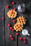 Belgian waffles with raspberries. Served with coffee pot and jug of milk over old wooden table. Flat lay Stock Photography