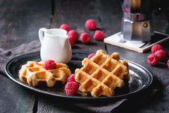 Belgian waffles with raspberries. Served with coffee pot and jug of milk on vintage tray over old wooden table Stock Image