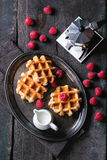 Belgian waffles with raspberries. Served with coffee pot and jug of milk on vintage tray over old wooden table. Flat lay Royalty Free Stock Photos