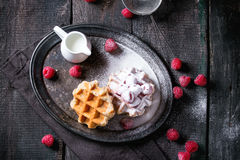 Belgian waffles with raspberries. And sugar powder, served with jug of milk on vintage metal tray with textile napkin over old wooden table. Dark rustic style Stock Images