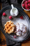 Belgian waffles with raspberries. And sugar powder, served with jug of milk on vintage metal tray with textile napkin over rusty surface. Dark rustic style Stock Image