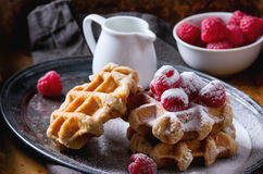 Belgian waffles with raspberries. And sugar powder, served with jug of milk on vintage metal tray with textile napkin over rusty surface. Dark rustic style Stock Images