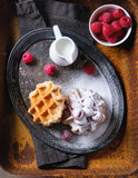 Belgian waffles with raspberries. And sugar powder, served with jug of milk on vintage metal tray with textile napkin over rusty surface. Dark rustic style Royalty Free Stock Photos