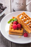 Belgian waffles with raspberries, topped with honey on a wooden. Table Royalty Free Stock Image