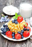 Belgian  waffles  with ricotta and berries on wooden table Royalty Free Stock Images