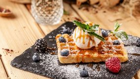 Belgian waffles with a scoop of ice cream, fresh berries raspberries, blackberries, blueberries and mint. Dusted with icing sugar stock photo