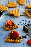 Belgian waffles in the shape of hearts with fresh strawberries and chocolate topping Royalty Free Stock Photos