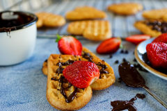 Belgian waffles in the shape of hearts with fresh strawberries and chocolate topping Stock Photos