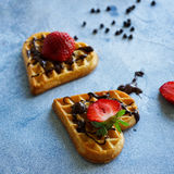 Belgian waffles in the shape of hearts with fresh strawberries and chocolate topping on blue table Stock Images